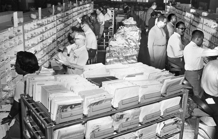 Clerks dig into the mountain of mail that descends on the city's main post office each day. Sun file photo taken May 14, 1961.