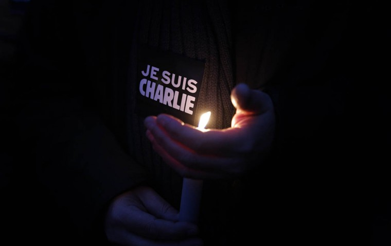 "A man holds a candle and a sticker reading "" I am Charlie"", during a demonstration in Paris. Three masked gunmen shouting ""Allahu akbar!"" stormed the Paris offices of a satirical newspaper, Charlie Hebdo, Wednesday, killing 12 people, including its editor, before escaping in a car. It was France's deadliest postwar terrorist attack. (Christophe Ena/AP photo)"