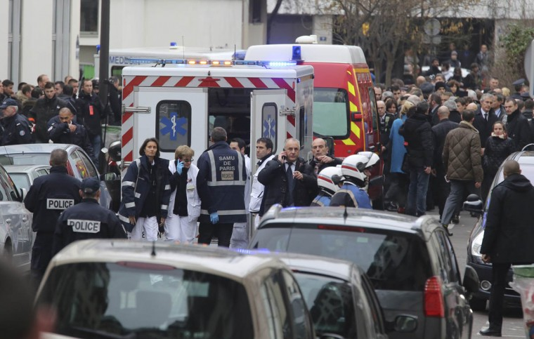 "Police officers and rescue workers gather at the scene after gunmen stormed a French newspaper, killing at least 12 people, in Paris, France, Wednesday, Jan. 7, 2015. Masked gunmen shouting ""Allahu akbar!"" stormed the Paris offices of the satirical newspaper Charlie Hebdo, killing 12 people, including the paper's editor and a cartoonist, before escaping in a getaway car. It was France's deadliest terror attack in at least two decades. (Remy de la Mauviniere/AP photo)"