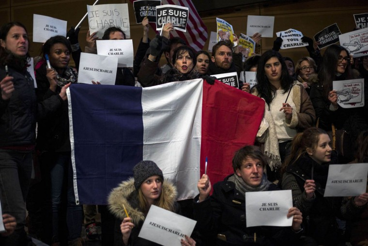 "People hold the French national flag and posters with the words ""Je Suis Charlie"" (I Am Charlie) outside the Newseum January 7, 2015 in Washington, DC in solidarity with the victims of the shooting at the Paris office of the satirical newspaper Charlie Hebdo by three gunman that took the lives of 12 people. (Brendan Smialowski/AFP photo/Getty Images)"