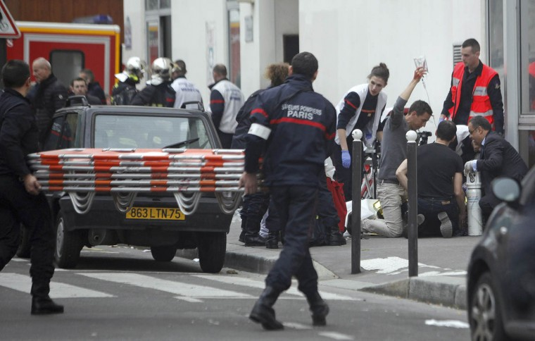 "An injured person is treated by nursing staff outside the French satirical newspaper Charlie Hebdo's office, in Paris, Wednesday, Jan. 7, 2015. France has raised its alert to the highest level after what President Francois Hollande said was a ""terror attack"" at the offices of a satirical magazine in Paris. Xavier Castaing, head of communications for the Paris police prefecture, has confirmed that at least 11 people were killed. (Thibault Camus/AP photo)"