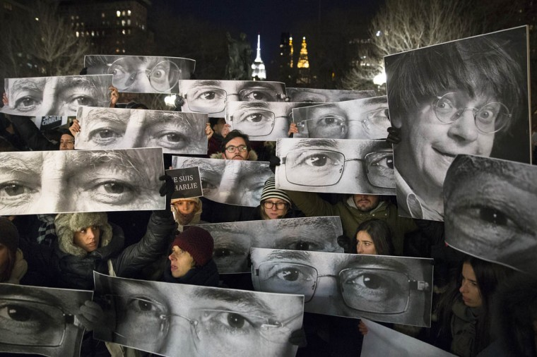 Mourners hold signs depicting victim's eyes during a rally in support of Charlie Hebdo, a French satirical weekly newspaper that fell victim to an terrorist attack, Wednesday, Jan. 7, 2015, at Union Square in New York. French officials say 12 people were killed when masked gunmen stormed the Paris offices of the periodical that had caricatured the Prophet Muhammad. (John Minchillo/AP photo)