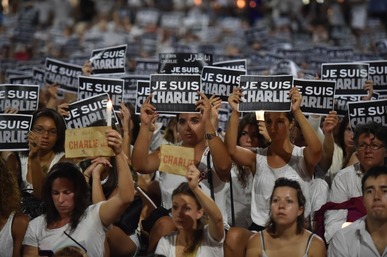 "Members of Sydney's French community gather in the heart of the city to hold aloft banners reading ""Je Suis Charlie"" (I am Charlie) on January 8, 2015, in tribute to the victims killed after gunmen opened fire in the offices of French satirical weekly Charlie Hebdo in Paris the day before. The vigil, just metres from where two hostages and a gunman died after a cafe siege in Sydney's Martin Place less than a month ago, saw many French and Australians carrying white and black ""Je Suis Charlie"" placards. Peter Parks/AFP/Getty Images"