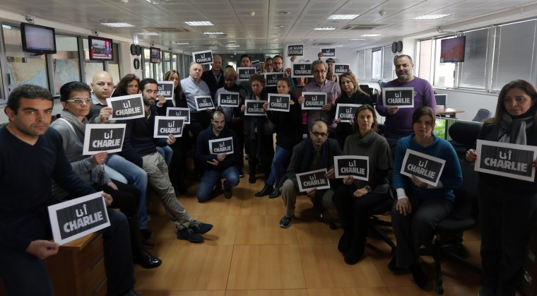 "Journalists of international press agency Agence France-Presse (AFP) hold signs reading ""Je suis Charlie"" (I am Charlie) in solidarity with the victims of an attack by armed gunmen on the offices of French satirical newspaper Charlie Hebdo on January 9, 2015 at the agency's Middle East and north Africa headquarters in Nicosia. Patrick Baz/AFP/Getty Images"
