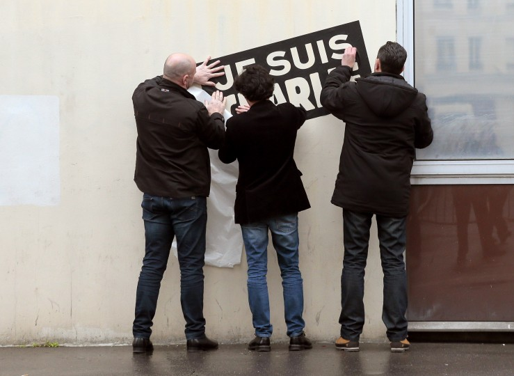 "People place on January 9, 2015 a ""Je suis Charlie"" (""I am Charlie"") sign outside the Charlie Hebdo magazine offices in Paris following the January 7 massacre at the weekly, which left 12 dead. France deployed elite forces in the hunt for two brothers accused of killing the 12 people in an Islamist attack on the satirical weekly. Elite police units are trying to establish dialog with two suspects in the Charlie Hebdo massacre holed up in a small business outside Paris with a hostage, an interior ministry spokesman said on January 9. The brothers were thought to have carried out the attack, the worst in France for half a century, in revenge for the weekly's repeated publication of cartoons mocking the Prophet Mohammed. Jacques Demarthon/AFP/Getty Images"