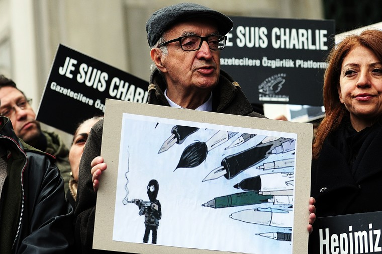 "Platform of freedom for journalist members hold cartoon and ""Je suis Charlie"" (""I am Charlie"") placards on January 9, 2015 as they observe a minute of silence in Istanbul for the victims of the January 7 massacre at the weekly, which left 12 dead. France deployed elite forces in the hunt for two brothers accused of killing the 12 people in an Islamist attack on the satirical weekly. Elite police units are trying to establish dialog with two suspects in the Charlie Hebdo massacre holed up in a small business outside Paris with a hostage, an interior ministry spokesman said on January 9. The brothers were thought to have carried out the attack, the worst in France for half a century, in revenge for the weekly's repeated publication of cartoons mocking the Prophet Mohammed. Ozan Kose/AFP/Getty Images"