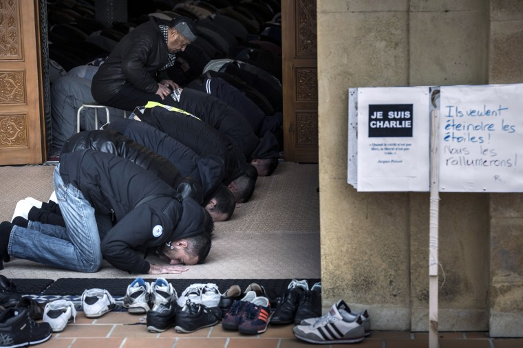 "Muslims pray in the Grande Mosque of Saint-Etienne for the Friday prayer next to a sign reading ""Je suis Charlie"", two days after an Islamist attack on French satirical magazine Charlie Hebdo by armed gunmen in which 12 died and 11 were injured, in the deadliest attack in France in half a century. Jean-Philippe Ksiazek/AFP/Getty Images"