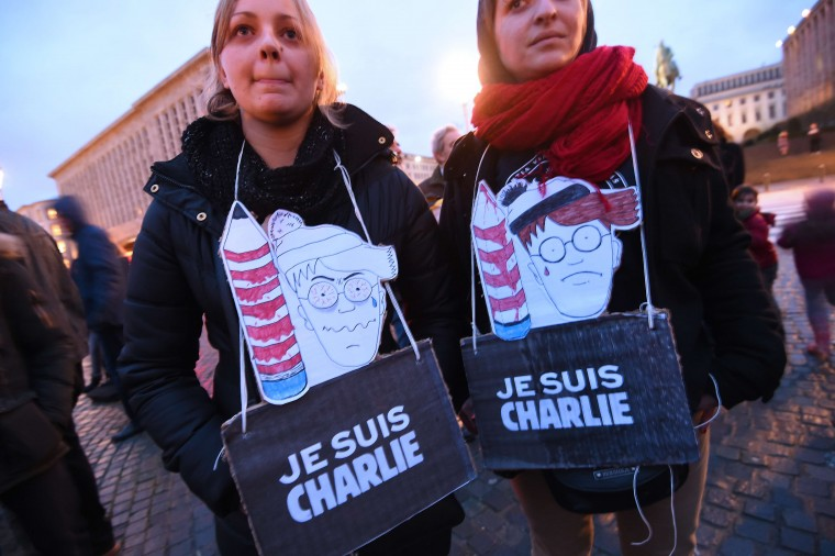 "Women wear signs reading ""Je suis Charlie"" (I am Charlie) during a gathering in Brussels on January 9, 2015 to pay tribute to the victims of a deadly attack on the Paris headquarters of French weekly Charlie Hebdo. Elite commandos units killed the two suspects in the Charlie Hebdo massacre during a simultaneous assault on the building they were holed up in and on a Paris Jewish supermarket, freeing hostages at both sites. Emmanuel Duand/AFP/Getty Images"