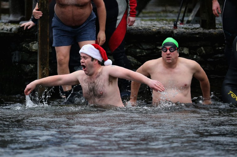 Swimmers take a dip in the icy waters of Lake Windermere during a charity swim to welcome in the New Year at Lake Windermere on January 1, 2015 in Windermere, England. The swim, organized by Sleekerswim, saw novice and veteran wild water swimmers plunge into the lake during heavy rain and high winds to raise cash for charity and welcome 2015. (Christopher Furlong/Getty Images)
