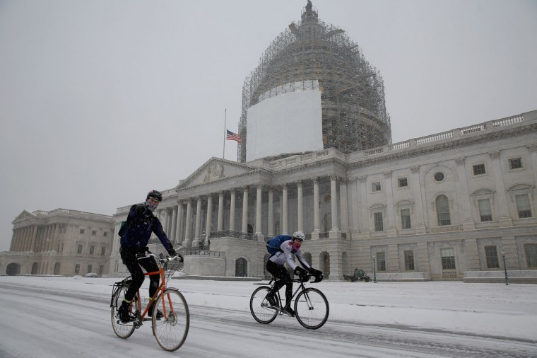 Bicyclists travel past the U.S. Captiol in falling snow as schools and business close due to unexpededly heavy precipitation January 6, 2015 in Washington, DC. Tuesday is the opening day of the 114th Congress. (Photo by Chip Somodevilla/Getty Images)