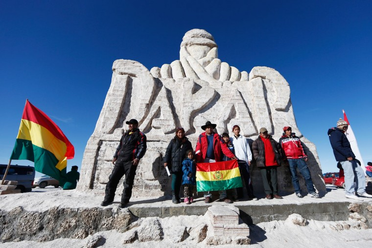 Tourists and locals pose near the large sculpture representing the Dakar Rally made using salt blocks during day 8 of the Dakar Rally on the Salar de Uyuni or Uyuni Salt Flats on January 11, 2015 in Uyuni, Bolivia. (Photo by Dean Mouhtaropoulos/Getty Images)
