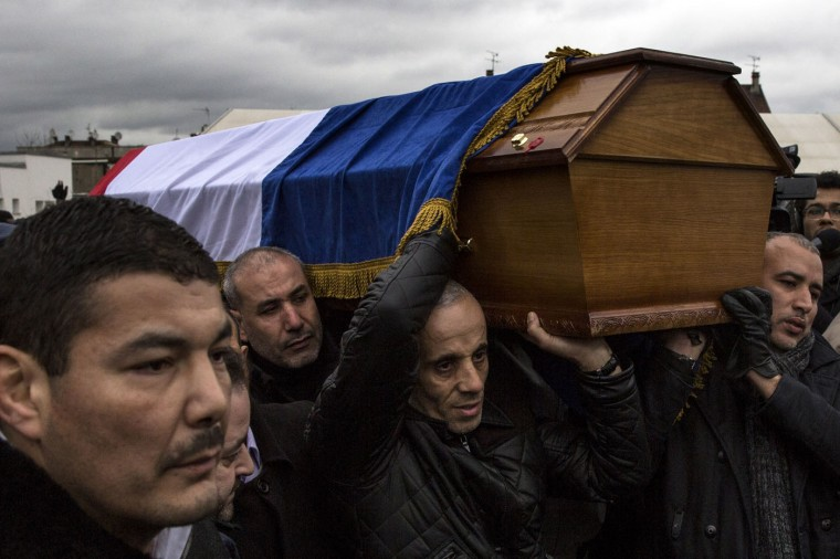 The funeral of murdered police officer Ahmed Merabet takes place at a muslim cemetery on January 13, 2015 in Bobigny, France. All three police officers killed in last weeks attacks have been awarded a posthumous Legion d'Honneur, in recognition of their bravery. The terrorist attacks began on Wednesday with the assault on the French satirical magazine Charlie Hebdo, killing 12, and ended on Friday with sieges at a printing company in Dammartin en Goele and a Kosher supermarket in Paris with four hostages and three suspects being killed. A fourth suspect, Hayat Boumeddiene, 26, escaped and is wanted in connection with the murder of a policewoman. (Photo by Dan Kitwood/Getty Images)
