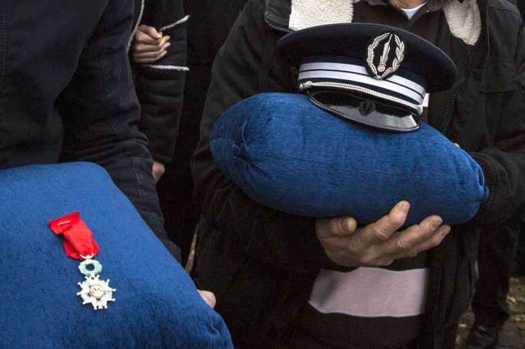 Family members of police officer Ahmed Merabet hold his cap and his Legion of Honor decoration during his funeral at a muslim cemetery on January 13, 2015 in Bobigny, France. All three police officers killed in last weeks attacks have been awarded a posthumous Legion d'Honneur, in recognition of their bravery. The terrorist attacks began on Wednesday with the assault on the French satirical magazine Charlie Hebdo, killing 12, and ended on Friday with sieges at a printing company in Dammartin en Goele and a Kosher supermarket in Paris with four hostages and three suspects being killed. A fourth suspect, Hayat Boumeddiene, 26, escaped and is wanted in connection with the murder of a policewoman. (Photo by Dan Kitwood/Getty Images)