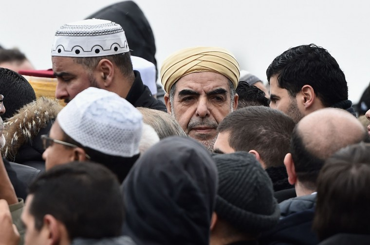 Imam Mohamed Hamdoui is seen during the funeral of police officer Ahmed Merabet as colleagues stand at a muslim cemetary on January 13, 2015 in Bobigny, France. The officers were awarded a posthumous Legion dHonneur, in recognition of their bravery. The terrorist attacks began on Wednesday with the assault on the French satirical magazine Charlie Hebdo, killing 12, and ended on Friday with sieges at a printing company in Dammartin en Goele and a Kosher supermarket in Paris with four hostages and three suspects being killed. A fourth suspect, Hayat Boumeddiene, 26, escaped and is wanted in connection with the murder of a policewoman. (Photo by Pascal Le Segretain/Getty Images)