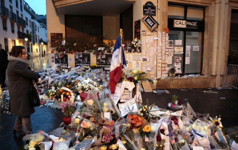 A woman looks early on January 9, 2015 at floral tributes left outside the Charlie Hebdo magazine offices in Paris for the victims of the January 7 massacre at the weekly, which left 12 dead. France deployed elite forces in the hunt for two brothers accused of killing the 12 people in an Islamist attack on the satirical weekly, as the pair spent a second night on the run despite a huge security operation. The brothers were thought to have carried out the attack, the worst in France for half a century, in revenge for the weekly's repeated publication of cartoons mocking the Prophet Mohammed. (Jacques Demarthon/AFP/Getty Images)