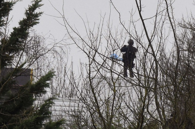 A French police officer stands on the roof of a building where two brothers suspected of slaughtering 12 people in an Islamist attack on French satirical newspaper Charlie Hebdo held one person hostage as police cornered the gunmen, in Dammartin-en-Goele, northeast of the capital, on January 9, 2015. The hostage drama unfolded at a printing business in the small town of Dammartin-en-Goele, only 12 kilometres (seven miles) from Paris's main Charles de Gaulle airport, police sources said. (Dominique Faget/AFP/Getty Images)