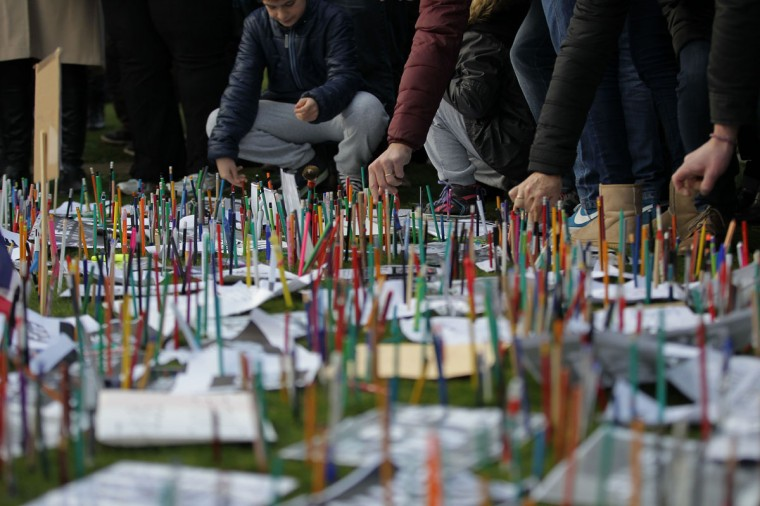 People put pencils on the ground in the War reporters' Memorial during a Unity rally Marche Republicaine on January 11, 2015 in Bayeux, northwestern France, in tribute to the 17 victims of the three-day killing spree. The killings began on January 7 with an assault on the Charlie Hebdo satirical magazine in Paris that saw two brothers killing 12 people including some of the country's best-known cartoonists and the storming of a Jewish supermarket on the eastern fringes of the capital which killed 4 local residents. A march with world leaders is taking place on January 11 through Paris in a historic display of global defiance against extremism after Islamist attacks that killed 17 victims. (Charly Triballeau/AFP/Getty Images)