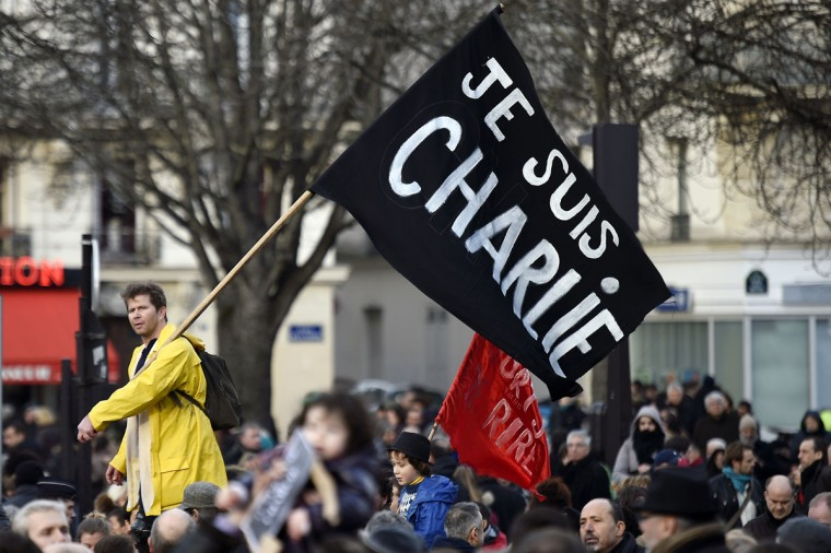 "A man waves a flag reading ""Je Suis Charlie"" (I am Charlie) during the Unity rally ""Marche Republicaine"" on January 11, 2015 in Paris in tribute to the 17 victims of a three-day killing spree by homegrown Islamists. The killings began on January 7 with an assault on the Charlie Hebdo satirical magazine in Paris that saw two brothers massacre 12 people including some of the country's best-known cartoonists, the killing of a policewoman and the storming of a Jewish supermarket on the eastern fringes of the capital which killed 4 local residents. (Martin Bureau/AFP/Getty Images)"