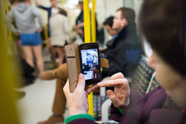 "A woman takes a photograph on her phone as people take part in the annual ""No Trousers On The Tube Day"" event in central London on January 11, 2015. Originally started in the US, the international event, also known as the ""No Pants Subway Ride"" was created by improvisation group ""Improv Everywhere"" and sees people taking train journies while wearing no trousers, yet acting as normally as possible. (Leon Neal/AFP/Getty Images)"