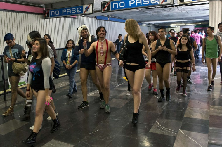 """People walk through a subway station during the worldwide 'No Pants Subway Ride' event in Mexico City on January 11, 2015. Originally started in the US, the international event known as the """"No Pants Subway Ride"""" was created by improvisation group """"Improv Everywhere"""" and sees people taking train trips wearing no trousers, yet acting as normally as possible. (Ronaldo Schemidt/AFP/Getty Images)"""