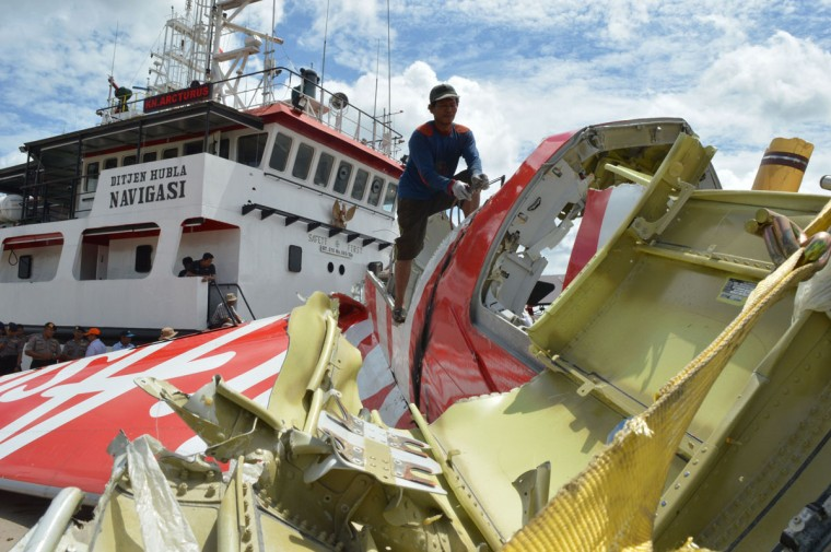 An Indonesian worker (top center) cuts the tail of the AirAsia flight QZ8501 in Kumai on January 12, 2015, after debris from the crash was retrieved from the Java sea. (AFP/Getty Images)