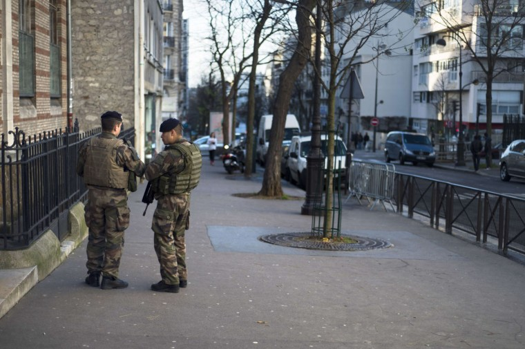 "French soldiers patrol on January 14, 2015 in front of a school in Paris, as France announced an unprecedented deployment of thousands of troops and police to bolster security at ""sensitive"" sites following last week's jihadist attacks in Paris.The alert level in shell-shocked France remained at its highest possible as the interior minister announced the deployment of nearly 5,000 police to guard Jewish schools and places of worship. (Martin Bureau/AFP/Getty Images)"