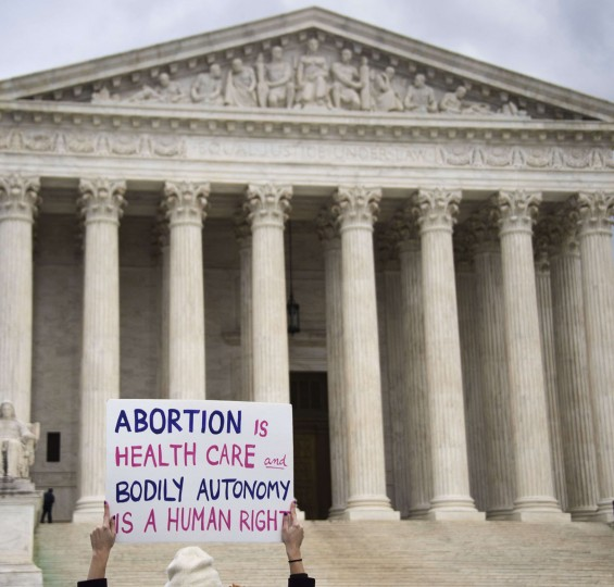 A pro-choice activist stands with a placard in front of the US Supreme Court in Washington, DC, January 22, 2015. (JIM WATSON/AFP/Getty Images)