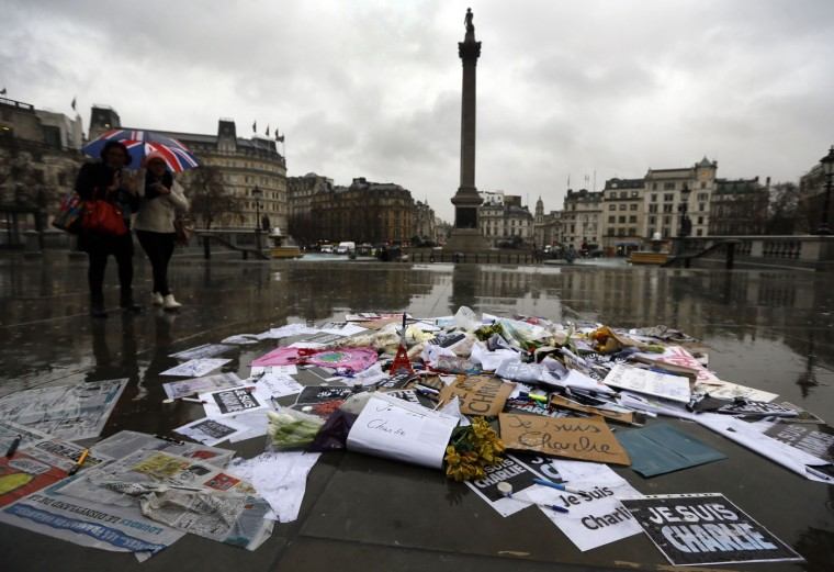Flowers and pens and placards lie after being placed to show solidarity with those killed in an attack at the Paris offices of weekly newspaper Charlie Hebdo, in Trafalgar Square, London, Thursday, Jan. 8, 2015. Masked gunmen stormed the Paris offices of a weekly newspaper that caricatured the Prophet Muhammad, methodically killing 12 people Wednesday, including the editor, before escaping in a car. It was France's deadliest postwar terrorist attack. (AP Photo/Kirsty Wigglesworth)