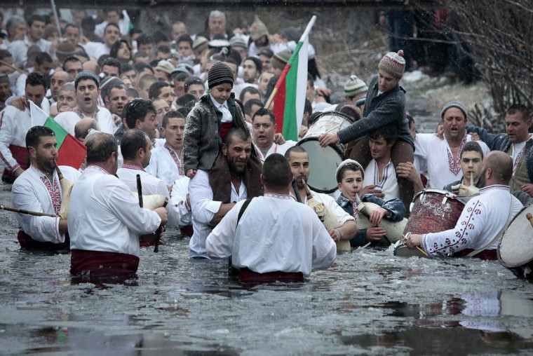 Believers sing and dance in the icy water of the river Tundzha as they celebrate Epiphany day, a Christian festival, in the town of Kalofer, Bulgaria, Tuesday, Jan. 6, 2015. Traditionally, an Eastern Orthodox priest throws a cross in the river and it is believed that the one who retrieves it will be healthy through the year. In the central Bulgarian town of Kalofer, hundreds of Christians marked Epiphany by donning national costumes and wading into the frigid waters of the Tundzha river. (AP Photo/Valentina Petrova)