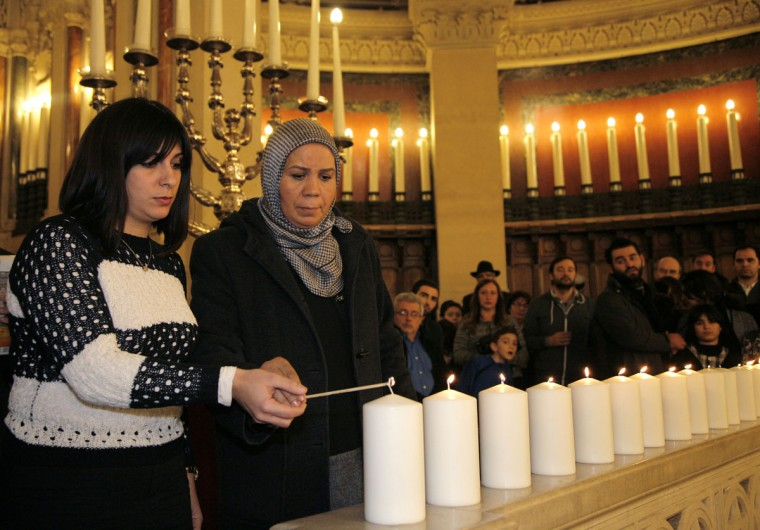 Latifa Ibn Ziaten, right, president of the Imad association and mother of French soldier Imad Ibn Ziaten who was killed by Islamist gunman Mohamed Merah, attends a ceremony at the Grand Synagogue in Paris, France, for all the victims of the attacks in Paris this week, which claimed 17 lives, Sunday, Jan. 11, 2015. (AP Photo/Matthieu Alexandre, Pool)