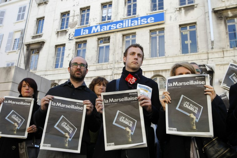 "Employees and journalists of the newspaper ""La Marseillaise"" hold a journal of the day, reading"" I am Charlie"" , in front of the newspaper building during a minute of silence , in Marseille, southern France, Thursday, Jan. 8, 2015, a day after masked gunmen stormed the offices of a satirical newspaper and killed 12 people. French police hunted Thursday for two heavily armed men ó one with a terrorism conviction and a history in jihadi networks ó in the methodical killing of 12 people at a satirical newspaper that caricatured the Prophet Muhammad. The prime minister announced several overnight arrests and said the possibility of a new attack ""is our main concern."" (AP Photo/Claude Paris)"
