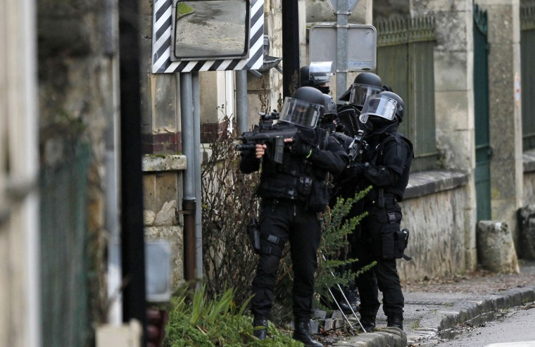 SWAT police officer patrol in the village of Longpont, north east of Paris, hunting down the two heavily armed brothers suspected in the massacre at Charlie Hebdo newspaper, Thursday, Jan.8, 2015. Scattered gunfire and explosions shook France on Thursday as its frightened yet defiant citizens held a day of mourning for 12 people slain at a Paris newspaper. (AP Photo/Michel Spingler)