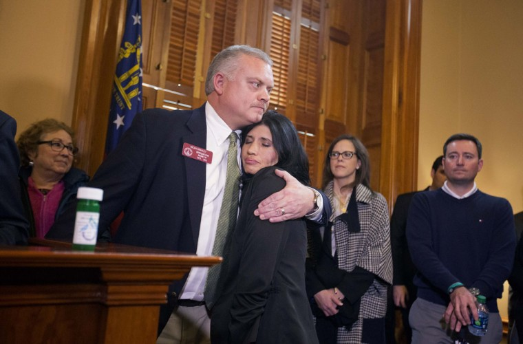 State Rep. Micah Gravley, R-Douglasville, left, embraces Melissa Davenport, who is diagnosed with multiple sclerosis, at a news conference after Gravley and Rep. Allen Peake, R-Macon, filed bill HB-1, which would legalize possession of cannabis oil for treatment of certain illnesses, Monday, Jan. 26, 2015, at the state Capitol in Atlanta. (AP Photo/David Goldman)