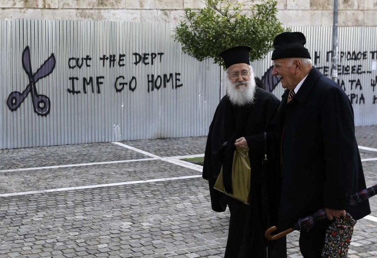A Greek Orthodox priest and an elderly man pass anti-austerity graffiti in front of Athens Academy on Thursday, Jan. 29, 2015. The European Parliament's president is to be the first European official to visit Athens, a day after announcements by Greece's nascent radical left government on rolling back a series of key budget commitments sent the country's stock market plummeting. (AP Photo/Thanassis Stavrakis)