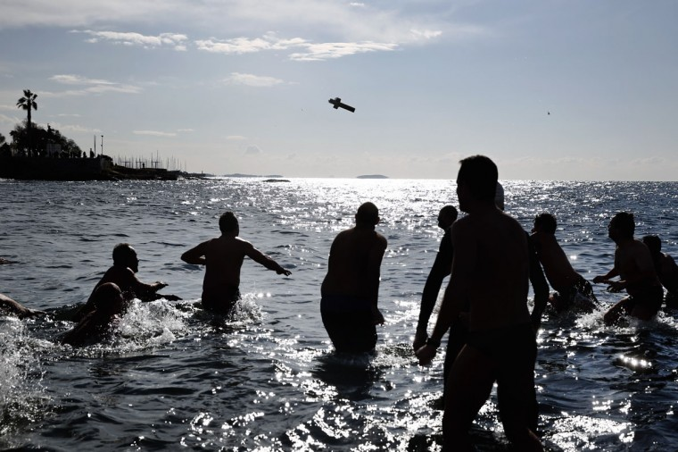 A wooden cross is seen in the air as swimmers try to retrieve it during a ceremony to bless the water in Greece's Flisvos beach, at Paleo Faliro near Athens on Monday, Jan. 6, 2015. Similar ceremonies to mark Epiphany were held across Greece on river banks, seafronts and lakes. An Orthodox priest throws a cross into the water and swimmers race to be the first to retrieve it. (AP Photo/Petros Giannakouris)
