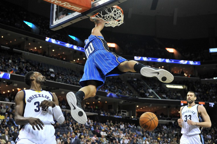 Orlando Magic forward Aaron Gordon (00) hangs from the rim after dunking the ball between Memphis Grizzlies forward Jeff Green (32) and center Marc Gasol (33) in the first half of an NBA basketball game Monday, Jan. 26, 2015, in Memphis, Tenn. (AP Photo/Brandon Dill)