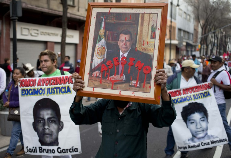 "A protestor carries a defaced portrait of the former governor of Guerrero state, Angel Aguirre, covered by the word in Spanish ""Assassin"" during a march marking the fourth month since the disappearance of 43 students from a rural teachers' college, in Mexico City, Monday, Jan. 26, 2015. Prosecutors have said police kidnapped the students on Sept. 26 in the southern state of Guerrero and handed them over to drug gang members, who killed them and burned the bodies. Protesters said Monday the government has failed to clear up doubts. (AP Photo/Eduardo Verdugo)"