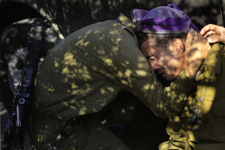 Israeli soldiers mourn during the funeral of Staff Sergeant Dor Chaim in Moshav Shtulim, southern Israel, Thursday, Jan. 29, 2015. Israeli Prime Minister Benjamin Netanyahu on Thursday said that Iran is to blame for a deadly flare-up along the Israeli-Lebanese border the previous day, the deadliest escalation in the disputed zone since the 2006 war between Hezbollah and Israel. (AP Photo / Tsafrir Abayov)