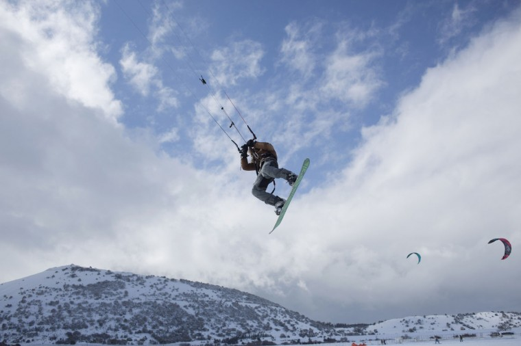 An Israeli kite surfer snow boards in the Israeli-controlled Golan Heights near the border with Syria, Thursday, Jan. 8, 2015. Snow fell in the Middle East as a powerful winter storm swept through the region. (AP Photo/Ariel Schalit)