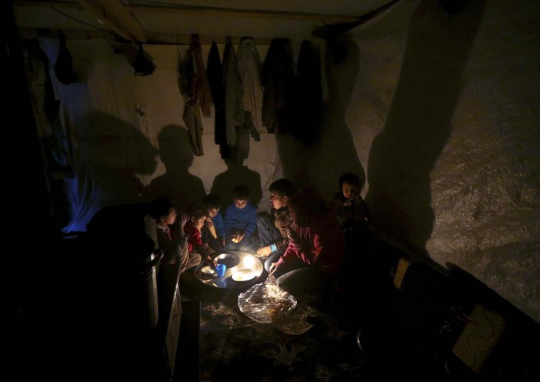 Syrian refugee children sit on the ground inside their tent home as they take their dinner at a Syrian refugee camp, in Deir Zannoun village in the Bekaa valley, eastern Lebanon, on Monday, Jan. 5, 2015. A snow storm is expected to hit Lebanon Monday affecting Syrian refugees, many of whom live in tents without heating. The government estimates there are about 1.5 million Syrians in Lebanon, about one-quarter of the total population. (AP Photo/Hussein Malla)
