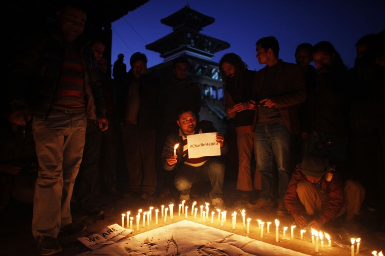 Nepalese journalists participate in a candlelight vigil in solidarity with victims of the attack on French satirical paper Charlie Hebdo, in Kathmandu, Nepal, Friday, Jan 9, 2015. (AP Photo/Niranjan Shrestha)