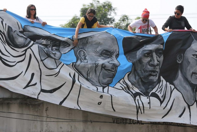 Filipino activists unfurl a painting with an image of Pope Francis as they prepare to welcome him during his visit to Manila, Philippines Thursday, Jan. 15, 2015. The Pope is set to arrive later Thursday for a pastoral visit which is expected to draw millions of faithful where about 81-percent of the population is Catholic. (AP Photo/Aaron Favila)