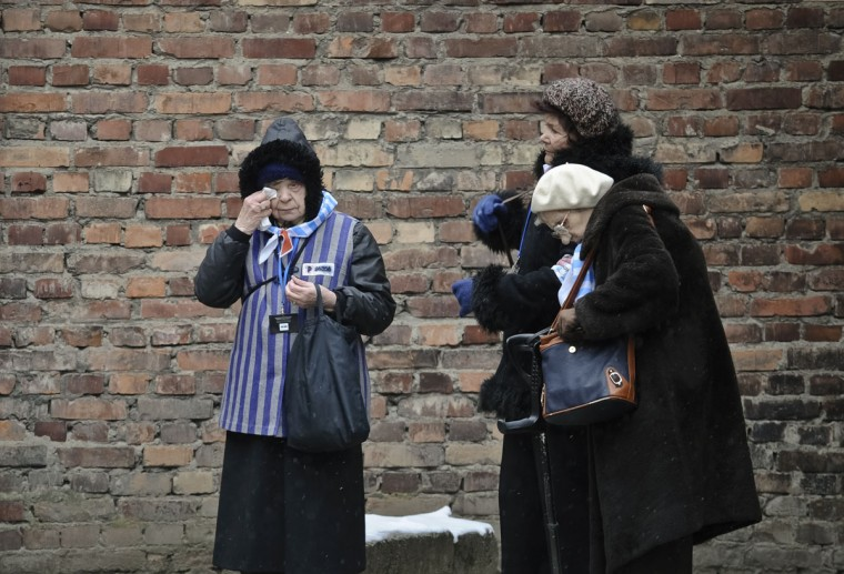 A Holocaust survivor wipes her eye while standing along with others outside a detention block of the Auschwitz Nazi death camp in Oswiecim, Poland, Tuesday, Jan. 27, 2015. Some 300 Holocaust survivors traveled to Auschwitz for the 70th anniversary of the death camp's liberation by the Soviet Red Army in 1945, down from 1,500 who attended the event 10 years ago.(AP Photo/Alik Keplicz)