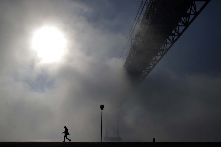 A man walks near the April 25th bridge by the Tagus riverbank in Lisbon on a foggy morning, Monday, Jan. 5, 2015. (AP Photo/Francisco Seco)