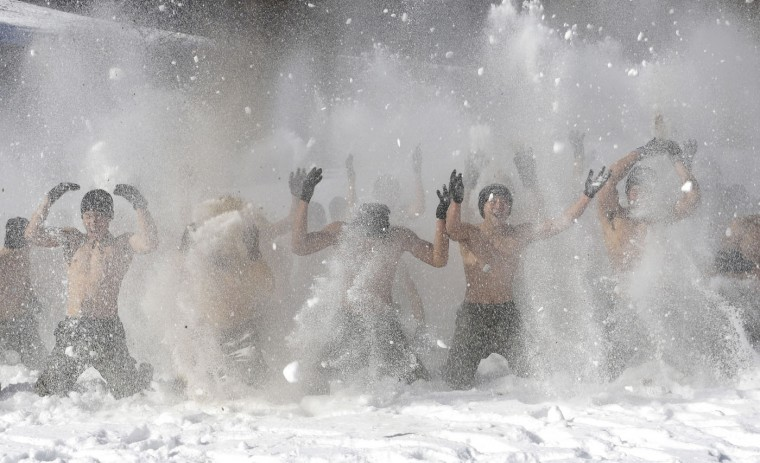 Half-naked soldiers from South Korea's Amry Special Warfare Command hurl snow during a winter exercise in Pyeongchang, South Korea, Thursday, Jan. 8, 2015. About 200 Special Warfare Command soldiers participate in this routine drill for the 2-week winter exercise. (AP Photo/Ahn Young-joon)