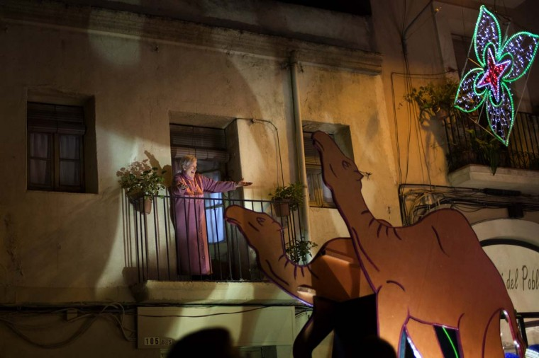 A woman reacts as one of the Three Wise Men passes by her balcony during the 'Cabalgata de Reyes,' or the Three Wise Men parade in Barcelona, Spain, Monday, Jan. 5, 2014. The traditional parade marks the eve of the Epiphany, a Christian holiday celebrating the story of the three wise men believed to have followed a bright star to offer gifts of gold, frankincense and myrrh to the newborn Jesus in Bethlehem. (AP Photo/Emilio Morenatti)