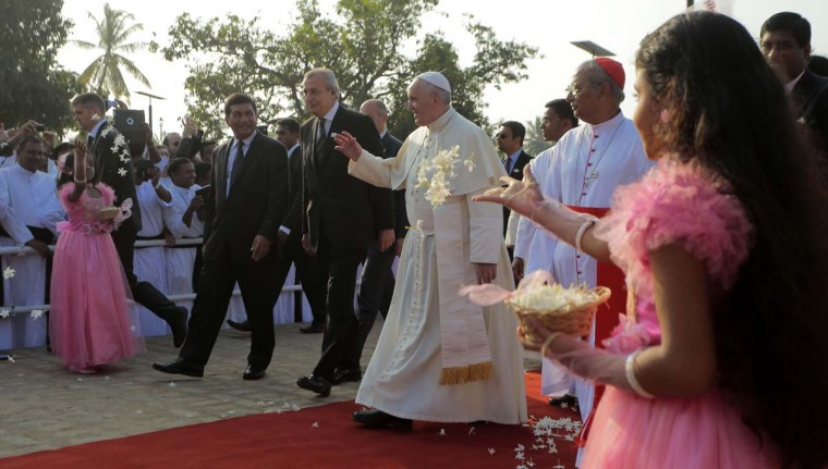"""Sri Lankan girls throw flowers towards Pope Francis as he arrives to visit the ëOur Lady of Lankaí chapel at the Benedict XVI Cultural Institute in Bolawalana, on the outskirts of Colombo, Sri Lanka, Thursday, Jan. 15, 2015. Pope Francis departed Sri Lanka Thursday for the Philippines, Asia's most populous Catholic nation, where ecstatic crowds await the first papal visit in 20 years. During his time in Sri Lanka, he traveled to the jungles of the war-torn north for a show of solidarity with the victims of the country's 25-year civil war, urging people to forgive one another """"for all the evil which this land has known."""" (AP Photo/Eranga Jayawardena)"""