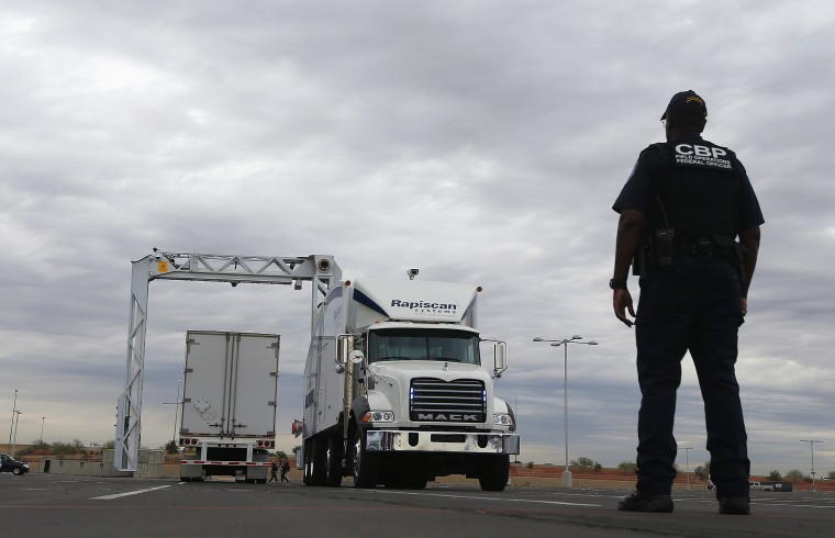 A U.S. Customs and Border Protection agent watches a truck-sized X-ray scanning machine, center, slowly scan a tractor-trailer at University of Phoenix Stadium, site of the NFL Super Bowl XLIX football game, during a security demonstration for the media Monday, Jan. 26, 2015, in Glendale, Ariz. The large mobile X-ray machines that are used to detect contraband and explosives are usually deployed at the U.S.-Mexico border. (AP Photo/Ross D. Franklin)