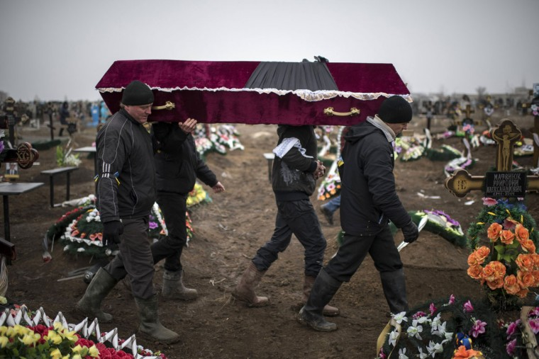 Ukrainian municipal woakers carry a coffin bearing the body of Vitaliy Sirotenko, who was killed Saturday during an attack in Mariupol, Ukraine, on Tuesday Jan. 27, 2015. A lull in the fighting in December had raised hopes for a peaceful settlement, but hostilities have escalated again in recent weeks as the rebels launched a series of new offensives. Russia has blamed the renewed fighting on the Ukrainian side, saying it has tried to settle the conflict by force. (AP Photo/Evgeniy Maloletka)