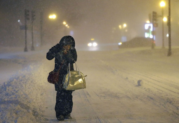 Denise Young, of Lynnfield, Mass., a nursing supervisor at Massachusetts General Hospital, adjusts her hood while walking to work, early Tuesday, Jan. 27, 2015, in Boston. New England is bracing for a blizzard threatening heavy snow, hurricane-force winds, and coastal flooding. (AP Photo/Steven Senne)